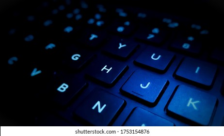computer keyboard closeup in blue backlight