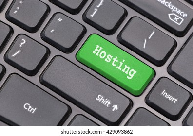 """Computer keyboard closeup with """"Hosting"""" text on green enter key"""