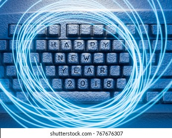 computer keyboard covered with snow illuminated by blue light with circles painted by blue light on a long exposure with the inscription happy new year 2018