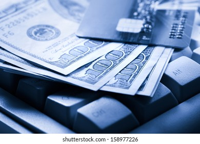 Computer keyboard, credit cards and dollars in cash