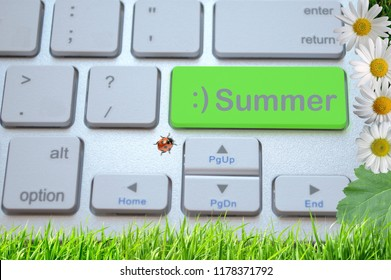 Computer keyboard with a green key Summer on a grass background