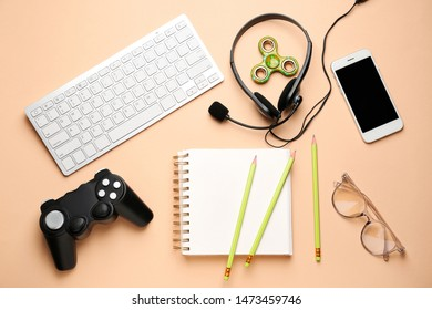 Computer keyboard with joypad, mobile phone, stationery and headphones on color background