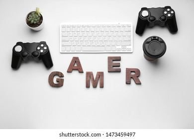 Computer keyboard with joypads, cup of coffee and word GAMER on white background