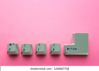 Computer keyboard keys with 2019 enter written using the white buttons on pink background. New year technology concept. New year 2019 card with copyspace.