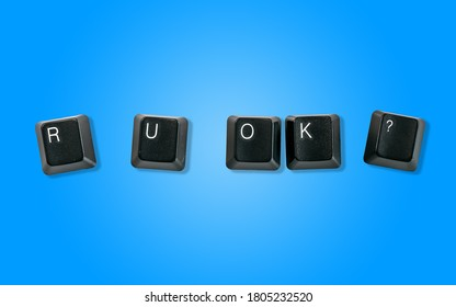 Computer keyboard keys spelling R U OK?, isolated on a blue background