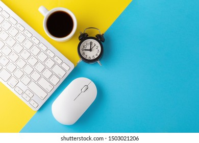 Computer keyboard and mouse with clock and coffee cup on yellow blue background, flat lay