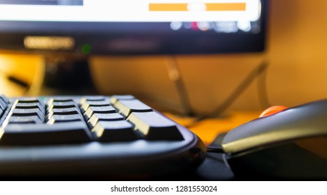 Computer keyboard , mouse and monitor perspective with bokeh background and colorful lights close up concept business technology