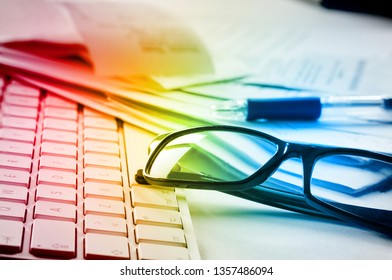 Computer keyboard, pair of glasses, pencil and messy papers lying on a table. Rainbow colored image in changing colors