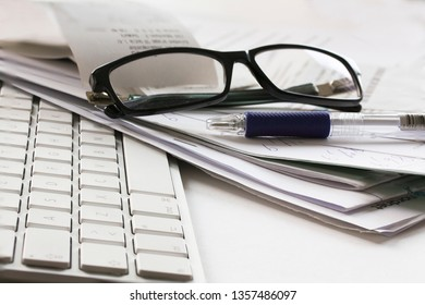 Computer keyboard, pair of glasses, pencil and messy papers lying on a white table