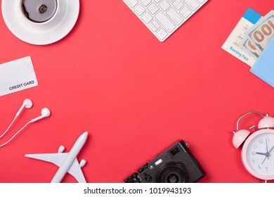 Computer keyboard, passport, plane model and credit card on red background.
