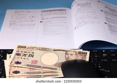 Computer keyboard and textbook and 10,000 yen bills.letter is japanese abc.