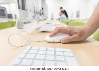Computer lab with pc desktop computer machine in blurry school class or office desk workspace with people at work with hand clicking on mouse