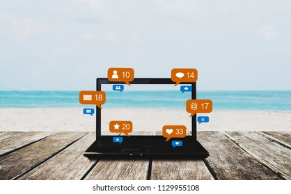 Computer laptop on wooden table at the beach in summer, with social media, social network notification icons