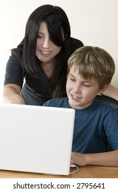 Computer learning education.  Adult woman helps a child sitting at the laptop computer.