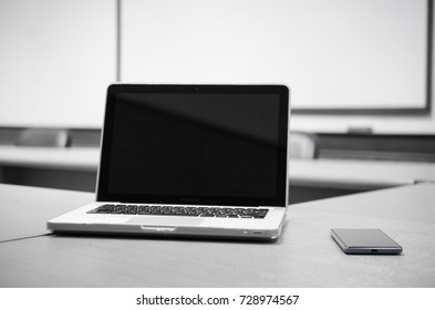 computer and mobile phone on wood table in the conference room with black and white tone,space for text.