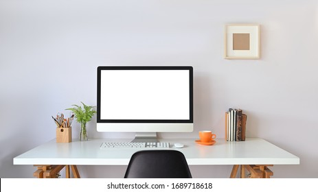 Computer monitor with white blank screen putting on working desk with wireless mouse, keyboard, pencil holder, stack of books, coffee cup and potted plant over white wall as background.