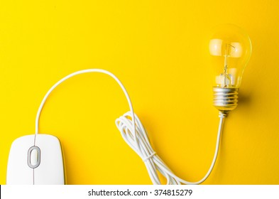 Computer mouse and bulb on a yellow background