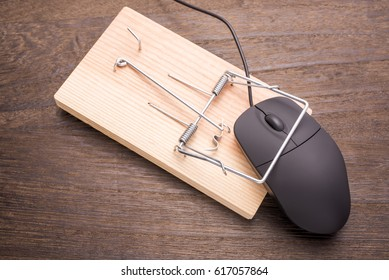 Computer mouse caught by the mousetrap device on wooden table
