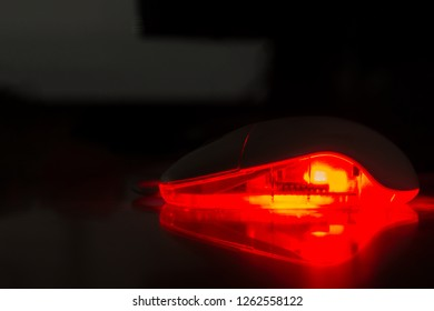 A computer mouse in the dark. The mouse is glowing, and components can be vaguely seen inside the mouse through translucent plastic. The light is reflected on the desk.