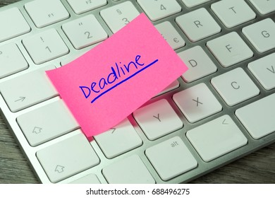 A computer and a note with the word Deadline