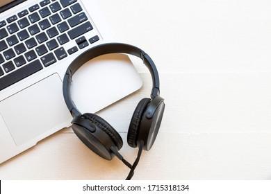 Computerheft mit schwarzem Kopfhörer zum Hören von Lifestyle auf weißem Holz