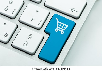 Computer notebook keyboard with icon shopping cart on key. E-commerce concept