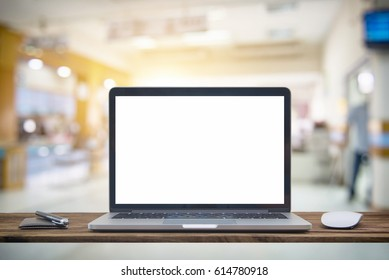 Computer notebook and mouse with Hospital blur Blurred image of patient waiting for see doctor. For background uses.