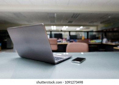 Computer notebook and smartphone on table in office room, out of focus photo.