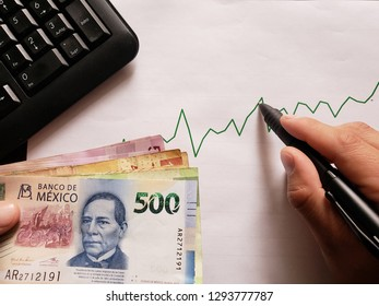 computer numeric keypad, graphic with ascending line, ballpoint pen, business man hand and mexican banknotes