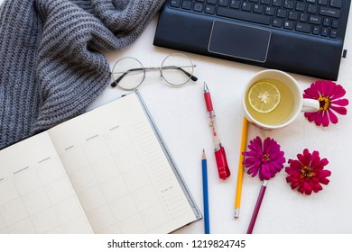 computer office supplies with notebook planner for business work and knitting wool scarf in winter season with hot honey lemon herbal healthy drinks on background white wooden