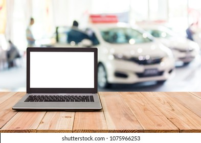 Computer on the table, blur image of car showroom as background.