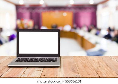 Computer on the table, blur image of conference room as background.