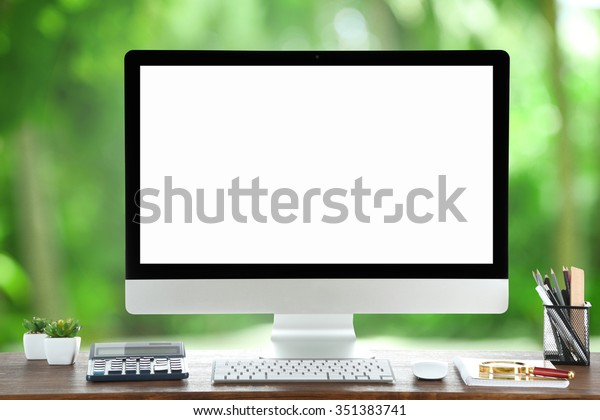 Computer on wooden table on nature green background