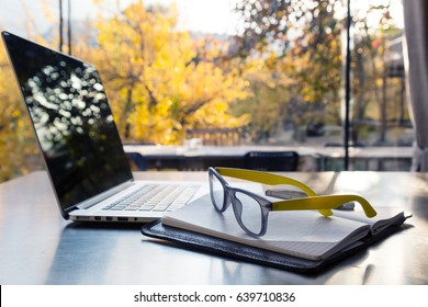 Computer Paper Notepad and other business items on black table against sunny view of garden outside of office