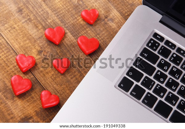 Computer with red hearts on table close up