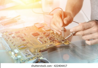 Computer repair service; hands of male tech testing motherboard