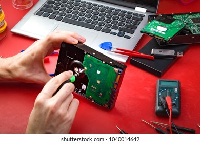 The computer repair specialist fix the HDD with special tools on the red table. Surrounding the repairman
