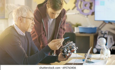 In Computer Science Class Teacher Examines programed Robot Engineered by His Student for School Project.