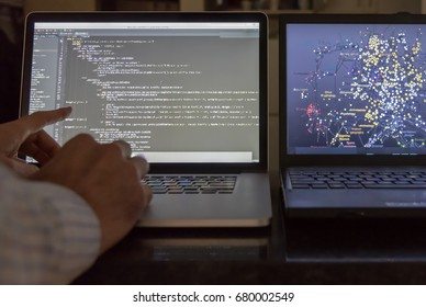 Computer scientist pointing at code screen with algorithmic data