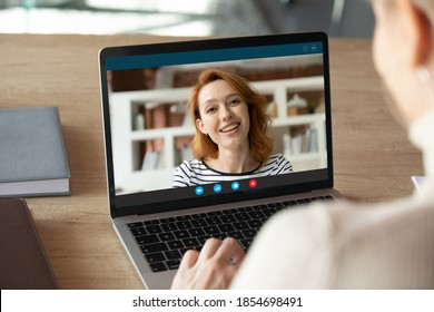 Computer screen close up view smiling attractive red-haired caucasian woman holding web camera video call with colleague, giving educational lesson or enjoying online conversation with friends.