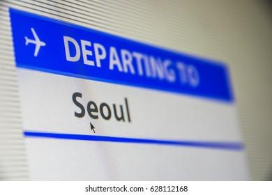 Computer screen close-up of status of flight departing to Seoul, South Korea