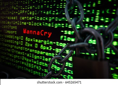 Computer screen display WannaCry message with blurred source code in background and locked chain. Concept of cyberattack by ransomware WannaCry
