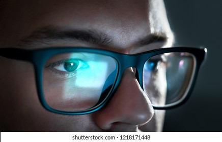 Computer screen light reflect from glasses. Close up of eyes. Business man, coder or programmer working late at night with laptop. Thoughtful focused guy in dark. Reflection of monitor. - Shutterstock ID 1218171448