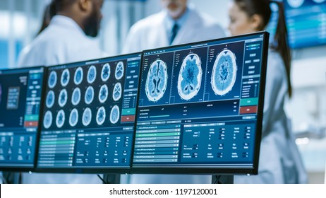 Computer Screen Showing MRI, CT Image Scan of the Brain. In the Background Meeting of the Team of  Medical Scientists in the Brain Research Laboratory. Neurologists / Neuroscientists Having Discussion
