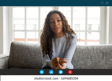 Computer screen view african woman sit on couch looking at webcam, share news with friend, applicant pass job interview by videoconference app, communicates with employer from home, video call concept - Shutterstock ID 1694685334