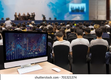 Computer set showing the Trading graph on the cityscape at night over the Abstract blurred photo of seminar room with attendee background,business and education concept
