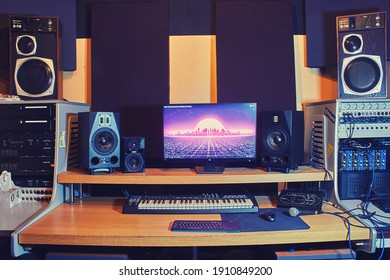 Computer, speakers and audio equipment on the table in the recording studio - Moscow, Russia, January 8, 2021