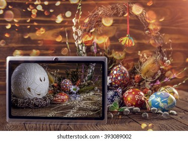 computer tablet, featuring the Easter themed image. Easter wreath in the background and wooden texture blurred. Easter, holiday, advanced technology. Happy Easter.