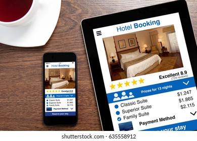 computer tablet and touch phone with app hotel booking screen on a wooden table