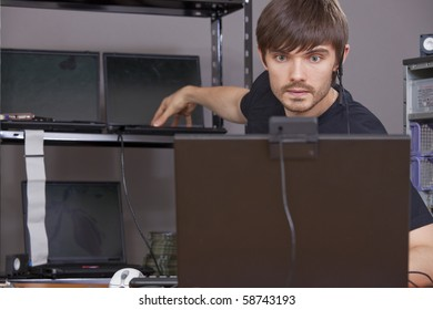computer technician with earphone working at laptops